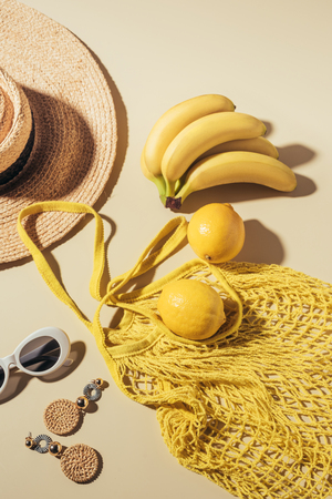 top view of wicker hat, sunglasses, earrings and yellow string bag with bananas and lemons 写真素材