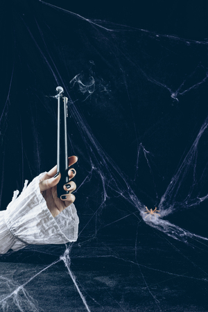 cropped view of mystic woman holding smoky candle in darkness with spider web Stock Photo