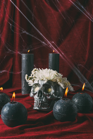 silver halloween skull with flowers and black candles on red cloth with spider web Stock Photo - 108244588