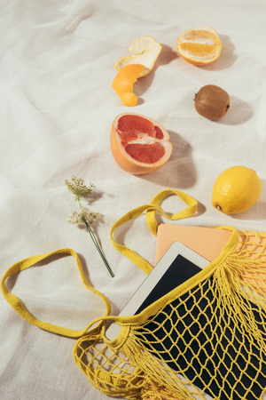 top view of tablet computer in yellow string bag and fresh ripe tropical fruits Stock Photo