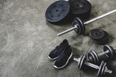 dumbbells and barbell with weight plates and sneakers on concrete floor