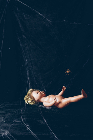 creepy doll in darkness with spider web