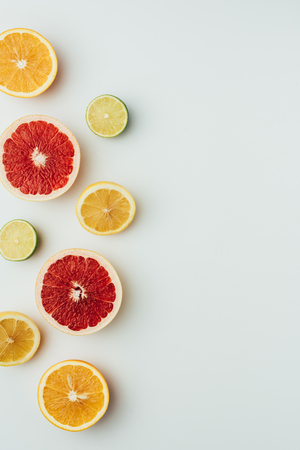 top view of grapefruit, lemon, lime and orange slices, on grey with copy space