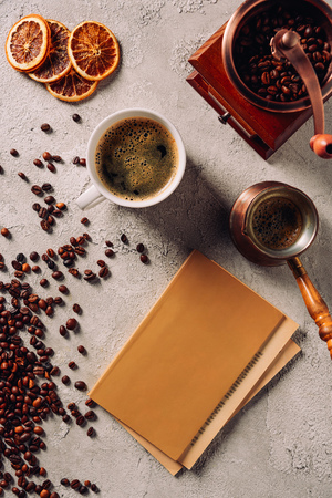 top view of cup and cezve of coffee with book and coffee grinder on concrete surface