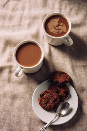 top view of cups of coffee with chocolate chip cookies on plate on beige cloth Stock Photo