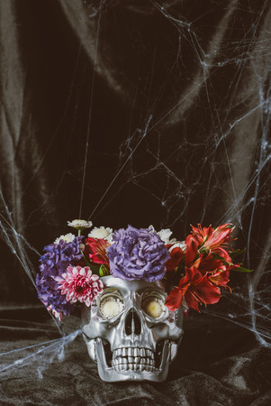 silver halloween skull with flowers on dark cloth with spider web Stock fotó