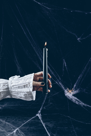 cropped view of scary woman holding black candle in darkness with spider web