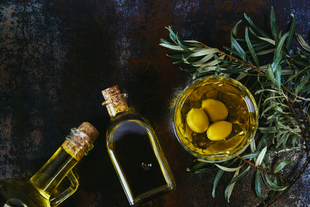 top view of glass jars with olive oil on shabby surface