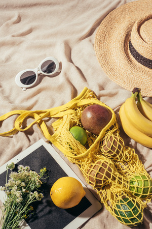 top view of straw hat, sunglasses, flowers, digital tablet and string bag with ripe fruits Stock Photo