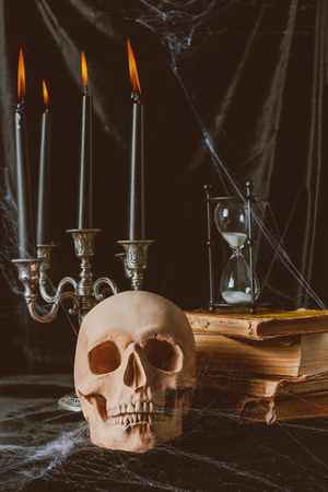 halloween skull, ancient books with hourglass and candles on black cloth Stock Photo
