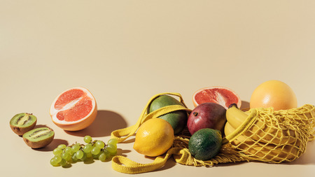 fresh ripe fruits and string bag on brown Stock Photo