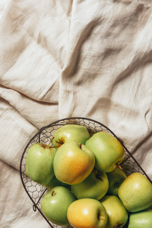 top view of green apples in metal basket on sacking cloth