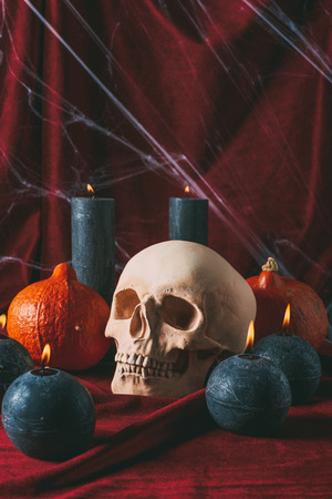 spooky skull, pumpkins and black candles on black cloth with spider web, halloween decorations Stock Photo