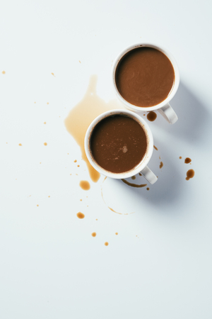 top view of cups of coffee standing messy on white surface
