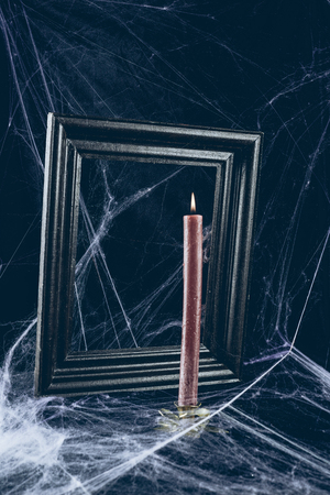 black frame and red candle in spider web, creepy halloween decor Фото со стока