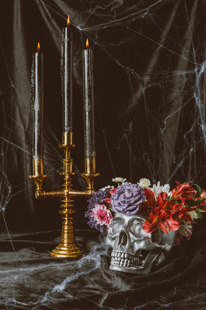 silver skull with flowers and candelabrum with candles on black cloth with spider web for halloween