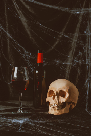 scary skull and red wine on black cloth with spider web Stock Photo