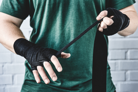 cropped shot of weight lifter wrapping hands before workout