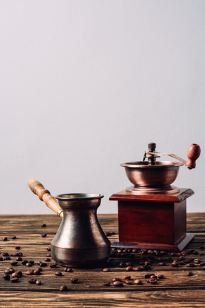 vintage cezve and coffee grinder with coffee beans on rustic wooden table 免版税图像