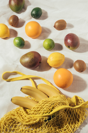 high angle view of yellow string bag and fresh ripe tropical fruits