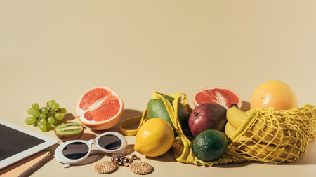 close-up view of sunglasses, earrings, digital tablet and ripe fruits in string bag on brown