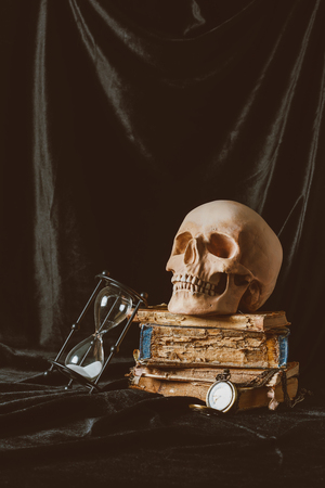 halloween skull on ancient books with sand clock on black cloth