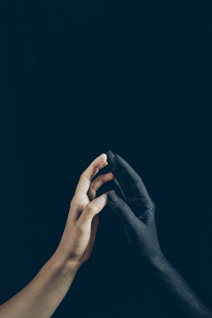 cropped view of woman touching with black demon hand isolated on black Stock Photo
