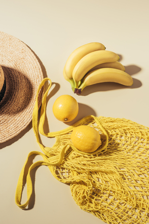 top view of straw hat and yellow string bag with lemons and bananas
