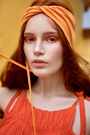 fashionable woman with red hair and makeup posing in orange headband Standard-Bild
