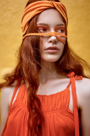 beautiful redhead woman with makeup posing in orange headband
