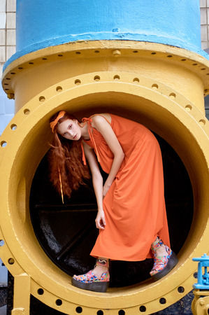 stylish girl with red hair posing in orange dress and headband in industrial pipe for fashion shoot