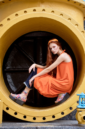 fashionable girl posing in orange dress and headband in industrial pipe Stockfoto