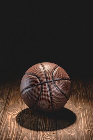 one brown basketball ball on wooden floor in dark room
