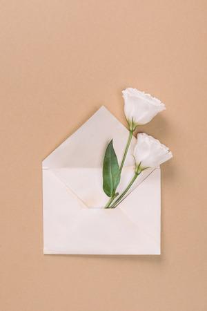 Top view of white eustoma flowers in envelope on beige background Zdjęcie Seryjne