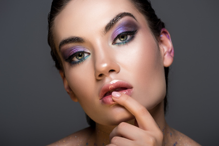 sensual thoughtful woman with glitter makeup, isolated on grey