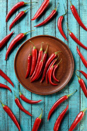 top view of red ripe chili peppers on plate and blue wooden table Archivio Fotografico - 108316926