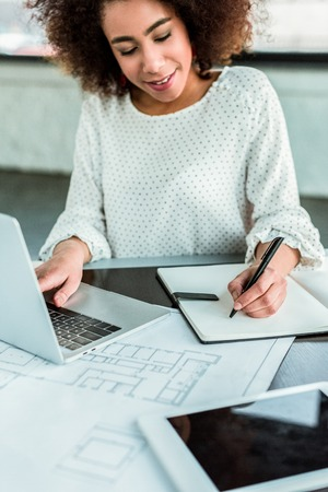 african american businesswoman using laptop and writing something to notebook in office