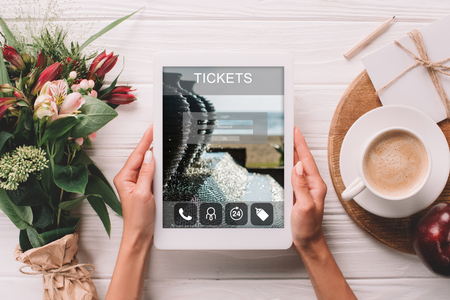 partial view of woman holding tablet with tickets website on screen at surface with cup of coffee and bouquet of flowers Stock Photo