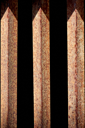 close up view of rust fence with black background behind Banco de Imagens