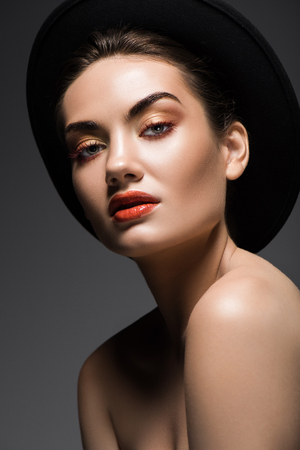 attractive model with makeup posing in elegant felt hat, isolated on grey Stok Fotoğraf - 108319231