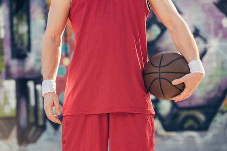 cropped image of basketball player standing with basketball ball on street 版權商用圖片