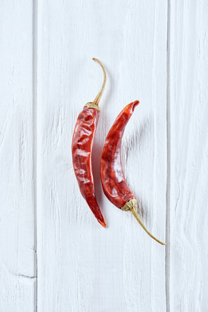 top view of chili peppers on white wooden surface Archivio Fotografico