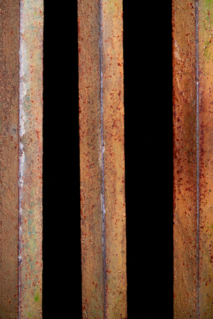 close up view of rust fence with black background behind Stock Photo