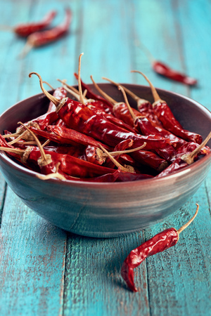 close up view of spicy chili peppers in bowl on blue wooden surface