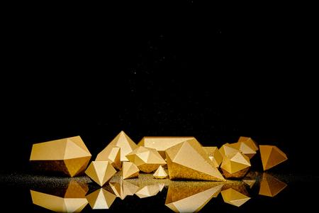 glanzende gefacetteerde gouden stukken en stof weerspiegeld op zwarte achtergrond