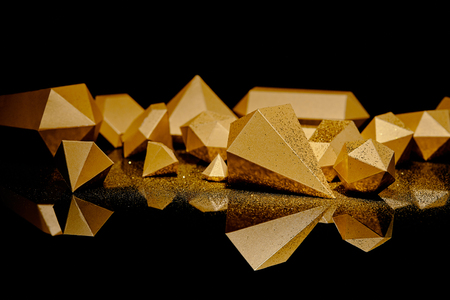 close-up view of shiny golden glittering pieces of gold reflected on black
