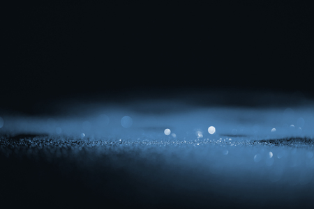 abstract shiny blue glitter on dark background