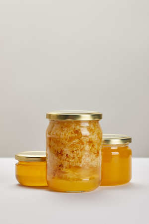 close up view of glass jars with honey on white surface on grey backdrop Reklamní fotografie