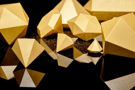 glinsterende gefacetteerde stukjes goud weerspiegeld op een zwarte achtergrond