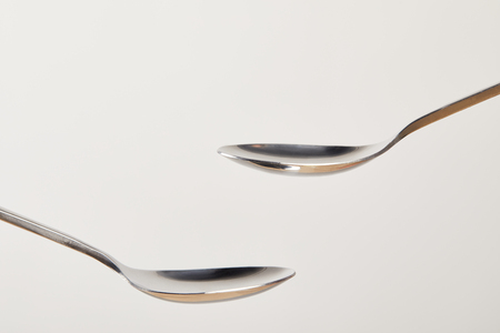 close up view of empty teaspoons on grey background